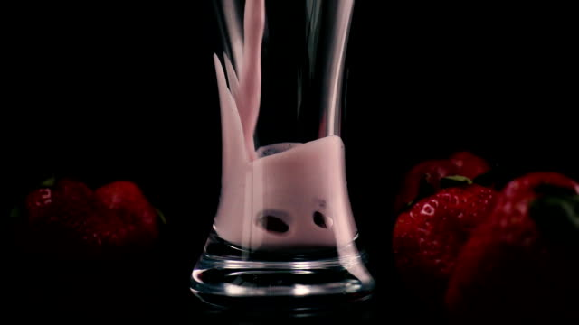 In a glass with strawberries pour a milkshake. Slow mo video
