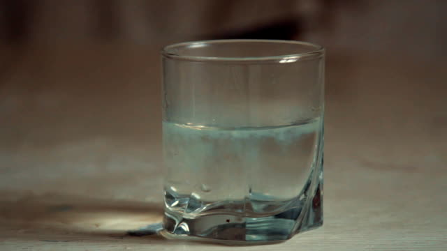 In a glass with water soluble medicine video
