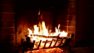 In an ancient stone fireplace fire burns video