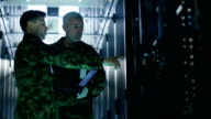 In Data Center Two Military Men Work with Open Server Rack Cabinet. One Holds Military Edition Laptop. video