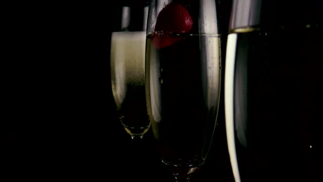 In glasses with champagne strawberries fall. Slow mo video