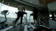 In Hong Kong, China in gym on treadmills running young woman and man video