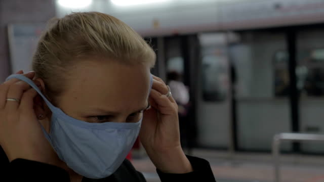 In Hong Kong, China in subway a young girl wears a medical mask video