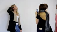 In model school young woman is having photo shoot video