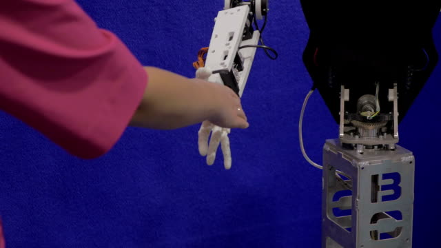 In Moscow, Russia on exhibition Robotix expo robot with arm shakes hands with girl video