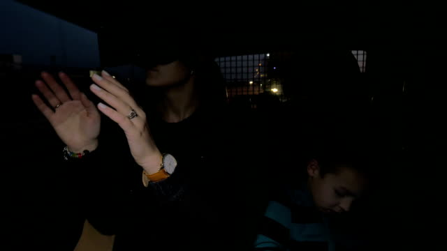 In Nea Kallikratia, Greece in car rides a young mother with virtual reality glasses and near sitting her little son video