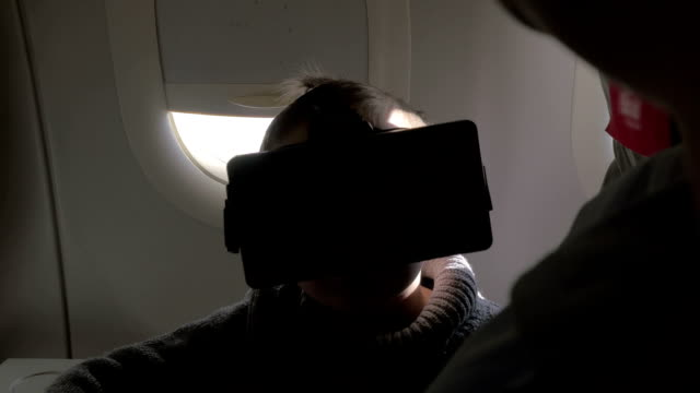 In plane sits a little boy with virtual reality glasses video