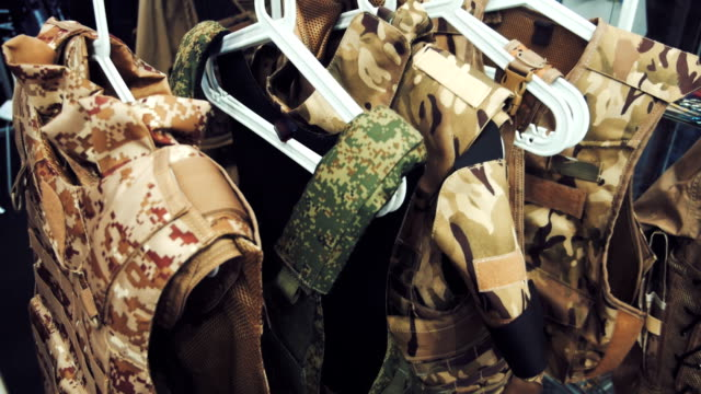 In the Army store on hangers hanging new bulletproof vests sand-colored and khaki color video