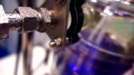 In the chemical laboratory glass flask with blue liquid are mixed via mixer video