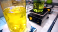 In the chemical laboratory glass flasks with yellow and green liquid are mixed video