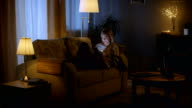 In the Evening Beautiful Young Woman Lies on the Couch and Uses Smartphone. Room Looks Warm and Cozy. video