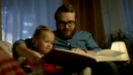 In the Evening Father and Little Daughter Sitting on a Sofa in the Living Room They are Reading Children's Book. video