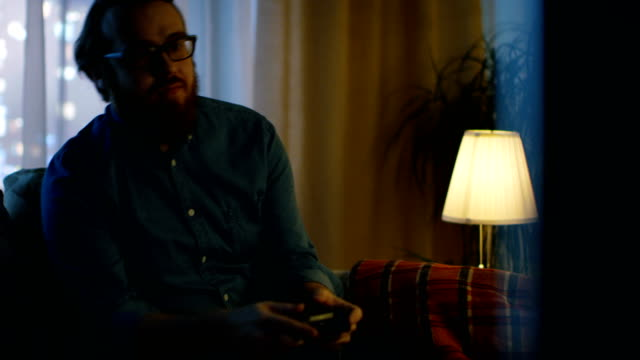 In the Evening Man is Sitting on a Sofa and Plays in Videogames In His Living Room. Big City is Seen Behind the Windows. video