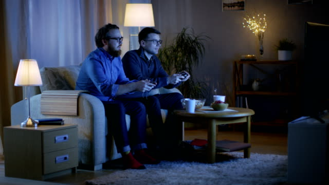 In the Evening Two Friends are Sitting on a Sofa in the Living Room and  Playing Competitive Video Games. They Push and Shove Each Other Friendly. video