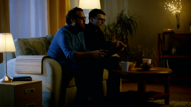 In the Evening Two Friends are Sitting on a Sofa in the Living Room and  Playing Competitive Video Games. video