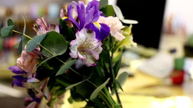 In the flower shop. Bouquet of irises in vase is on the table. video
