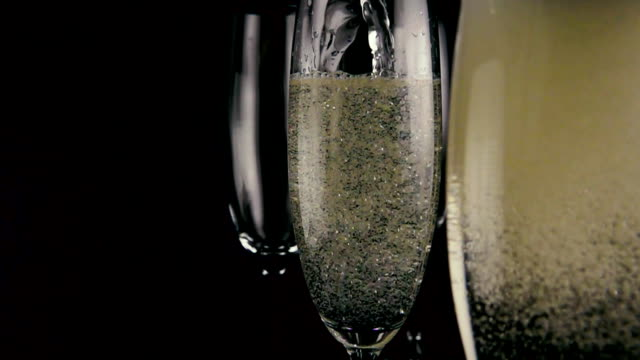 In the foreground a glass of champagne with bubbles out of focus. Slow mo video