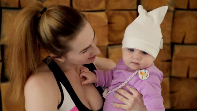 In the interval between training, a young mother plays with her baby video