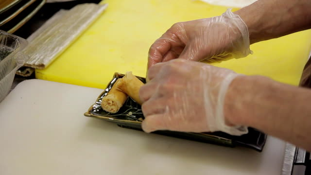 In the kitchen, the cook in gloves puts on a long plate rolls video