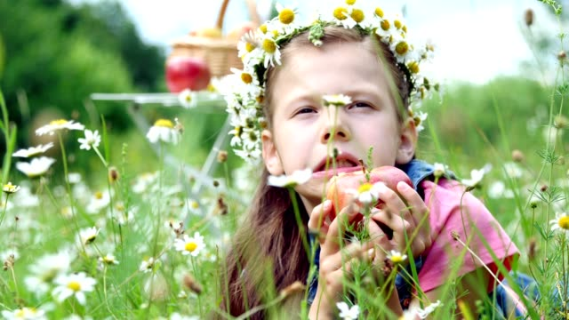 In the middle of a chamomile lawn, in the grass lies a pretty girl of seven years, in a wreath of daisies, and gaily with an apetite gnawing, eating a red apple video