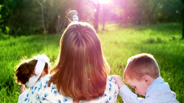 In the rays of the sun, against the light, at sunset, in the summer in the park, a young mother, a blond woman blows soap bubbles for her children, her two sons. Boys are fun, interesting video