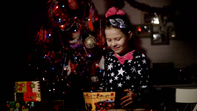 In the twilight of the night, a pretty blonde girl with a pink bow in her hair , in a a beautiful dress admires Christmas presents, opens a large box, filling the room with a magical glow, she is happy, glad. In the background is a Christmas tree in color video
