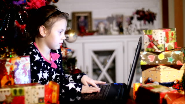 In the twilight of the night, among the gifts in bright colorful paper packages, the pretty blonde girl with a pink bow in her hair and in a beautiful dress is typing a letter to Santa Claus, Father Christmas, Father Moroz on her laptop. In the background video