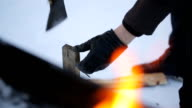 In winter, a man wearing gloves chopping wood with an ax on a background of fire video