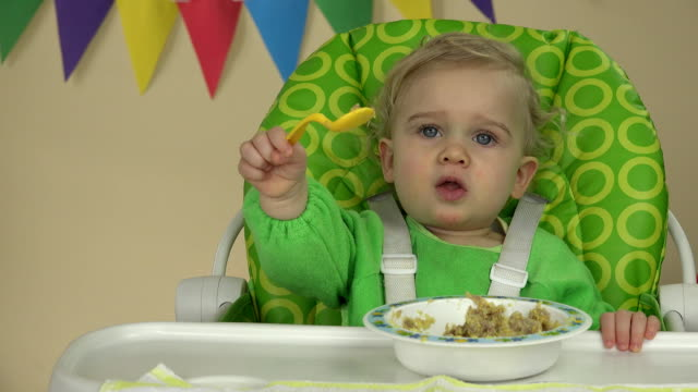 Independent baby boy with spoon sits at feeding chair and eats porridge video