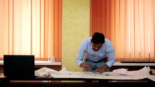 Indian architect draws a blueprint leaning over the table video