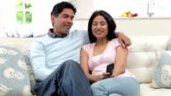 Indian Couple Sitting On Sofa Watching TV Together video