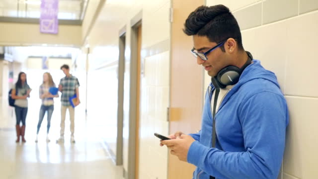 Indian high school male student texting on smart phone while standing in hallway video