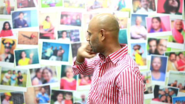 Indian man showing photographs on the Wall and explaining video