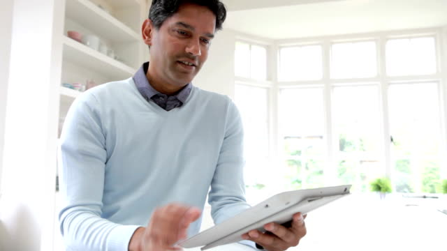 Indian Man Using Digital Tablet In Kitchen At Home video