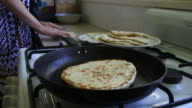Indo-Fijian woman cooking homemade Naan bread in the kitchen video