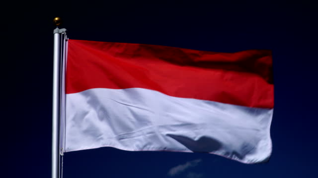 4K: Indonesian Flag on Flagpole in front of Blue Sky outdoors (Indonesia) video