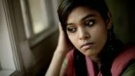 Indoor close-up of serene Asian teenager girl sitting near window. video