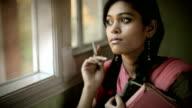 Indoor, serene Asian teenage girl student near window with books. video