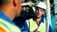 Industrial engineer and worker discussing in factory. Close-up video