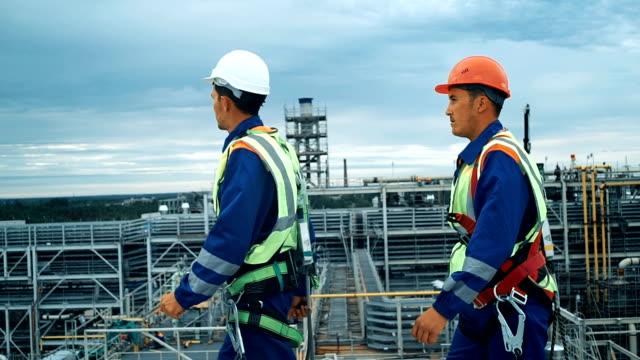 Industrial engineers walking across the top edge of a roof. video
