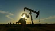 Industrial jack pump platform pumping crude oil over sunset sun video