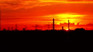Industrial orange sunset. Sun goes down behind pipes and power pylons. FullHD real time long shot video
