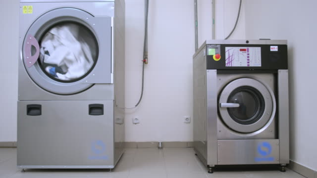 Industrial washer dryer working. Hotel laundry service. Clothes dryer machine video