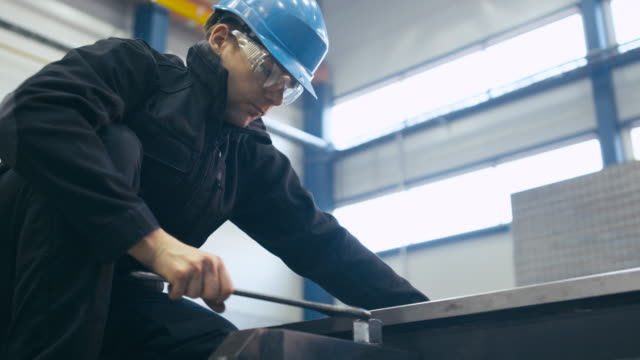 Industrial worker is tightening screws with a wrench at a factory. video