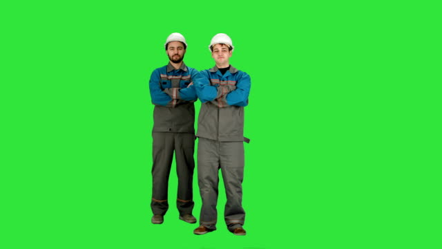 Industry, building, construction and people concept - happy male builders on a Green Screen, Chroma Key video