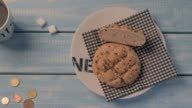 Inexpensive bun, a cup of coffee and two slices of sugar on a blue wooden table. The minimum cost. video