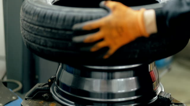 Inflating car tire. Auto mechanic controls the pressure. video