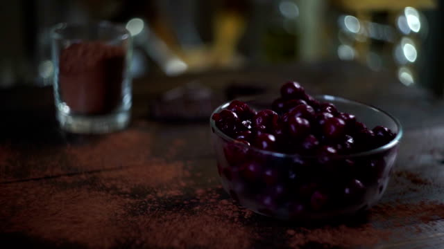 Ingredients for baking brownie cake. Cherry in glass bowl. Cocoa powder in glass video