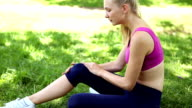 Injured fit blonde touching her knee on the grass video