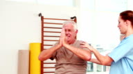 Injured senior citizen exercising with physiotherapist video